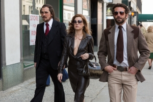 "Francois Duhamel/Annapurna Productions  Irving Rosenfeld (Christian Bale), Sydney Prosser (Amy Adams) & Richie Dimaso (Bradley Cooper) walk down Lexington Avenue n ""American Hustle."""